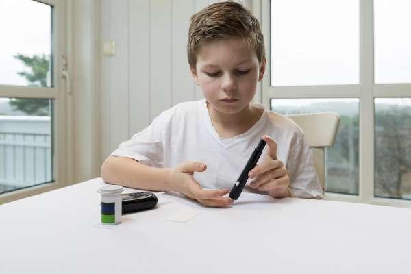 Child testing blood glucose